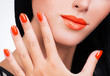 Closeup female hand with beautiful orange nails at woman's face