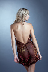 Sexy slim blonde posing in dress with decollete