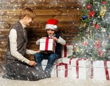 Mother and her lIttle boy in Santa hat opening gift box