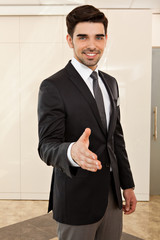 handsome business man smiling inviting to a handshake