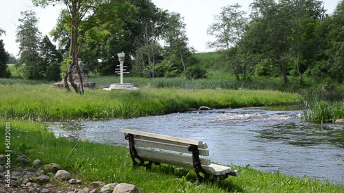 flowing stream in the grass stands solitary white wooden bench