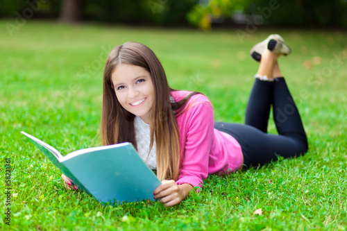 Female student reading a book lying on the grass