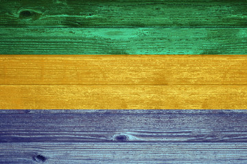 Gabon Flag painted on old wood plank background.