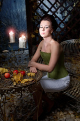 beautiful brunette girl with candles in mystical autumn garden
