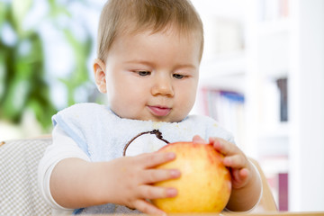 Cute baby boy holding an apple in his hands.