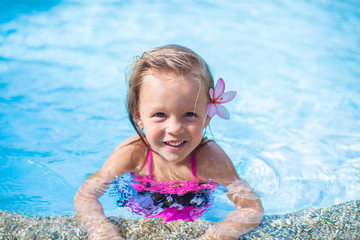 Little cute happy girl with flower behind her ear has fun in the