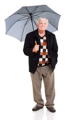 senior man standing under an umbrella