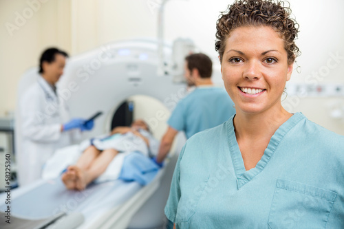 Nurse With Colleague And Doctor Preparing Patient For CT Scan