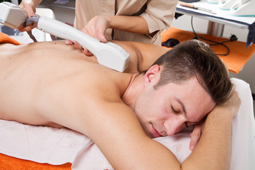 young man receiving laser epilation on beauty center