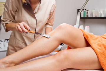 Beautician waxing a woman's leg