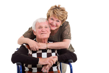 elderly wife hugging handicapped husband