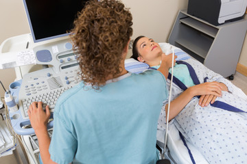 Nurse Performing Ultrasound Scan On Patient's Neck