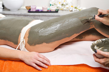 relaxing woman lying on a massage table receiving a mud treatmen