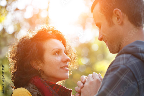 Loving couple in the park looking at each other in the sunlight