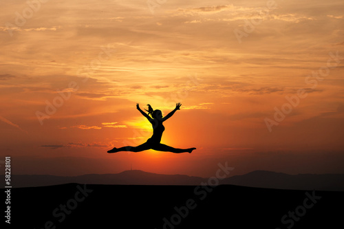 the splits by female gymnast in sunset