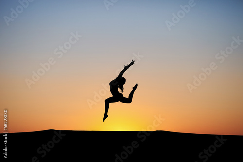 silhouette of female dancer in sunset sky