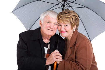 senior husband and wife under an umbrella
