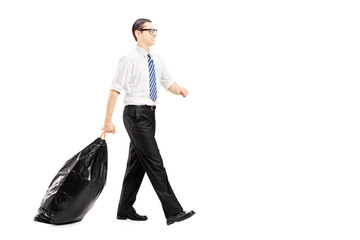 Young male carrying a garbage bag and walking