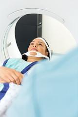Patient Undergoing CT Scan In Examination Room