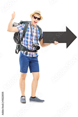 Hiker with backpack holding a big arrow and giving thumb up