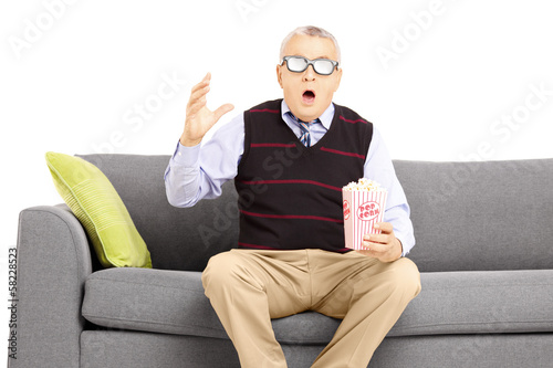Shocked senior man sitting on a sofa and watching movie