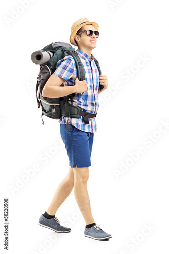 Full length portrait of a male hiker with backpack walking