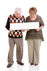 retired couple holding white banner