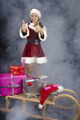 Weihnachtsfrau mit Geschenken auf dem Schlitten im Nebel
