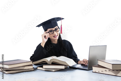 Isolated young graduate using her laptop