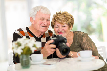 senior couple viewing pictures on camera