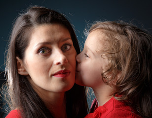 Daughter kisses her mother in her cheek