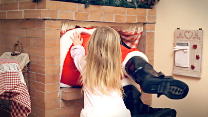 Christmas Eve little girl push Santa Claus in fireplace