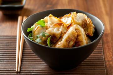 Closeup of fried gyoza (potstickers) in a bowl.