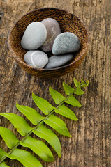 zen stones in bowl  and fern leaf on old wood background