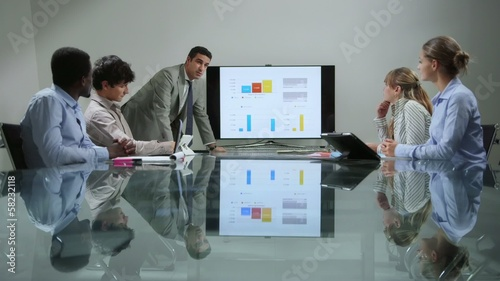group of men and women at office meeting during presentation