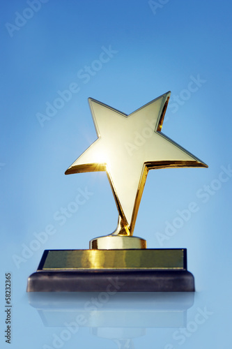 Gold star award on the stand against blue background