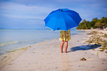 Little cute girl with umbrella on exotic beach