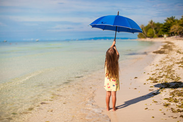 Little cute girl with big blue umbrella walking on a tropical