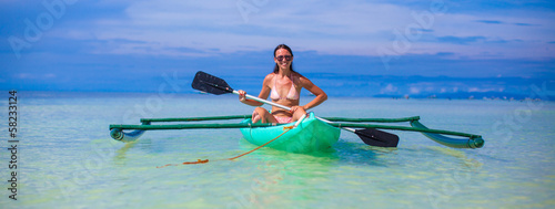 Young woman kayaking alone in the clear blue sea