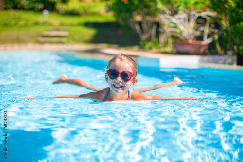 Little adorable happy girl swims in the swimming pool