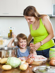 woman with little girl cooking together