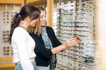 Happy Woman With Salesgirl Examining Eyeglasses