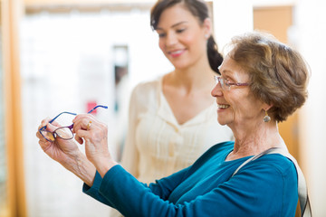 Senior Woman Holding New Glasses In Store