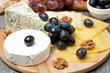 Assorted cheese and grapes on a wooden board
