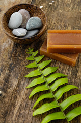 stones in bowl and fern leaf, soap on old wood