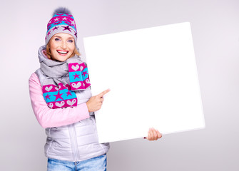 Adult smiling  woman in winter hat holds the white banner