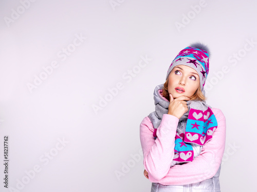 Photo of a thinking girl in winter clothes looking up