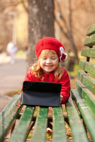 Happy smiling little girl using tablet