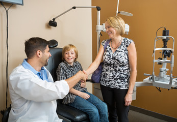 Optician And Woman Shaking Hands While Looking At Boy