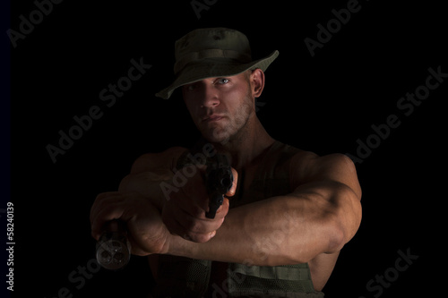 Soldier holding gun and flashlight.